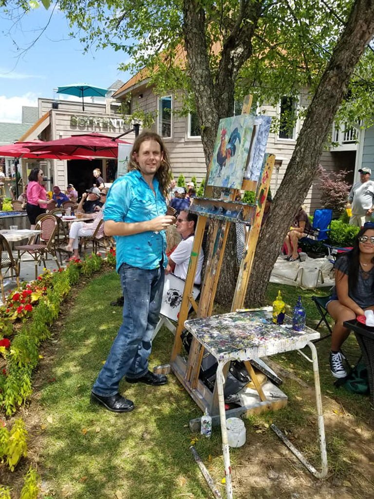 Avery County Wine & Beer Festival 2018.  Artist Kent Paulette painting live at Banner Elk Art Gallery during the festival.  It is a sunny day.  He is painting a rooster on his easel which is in the shade under a tree.  He is surrounded by people listening to music and watching him paint at the festival in downtown Banner Elk, NC.  The sky is blue and there are flowers around the easel.  K. Paulette is smiling and wearing jeans and a teal shirt.  He has long hair.  Sorrento's Bistro is in the background.