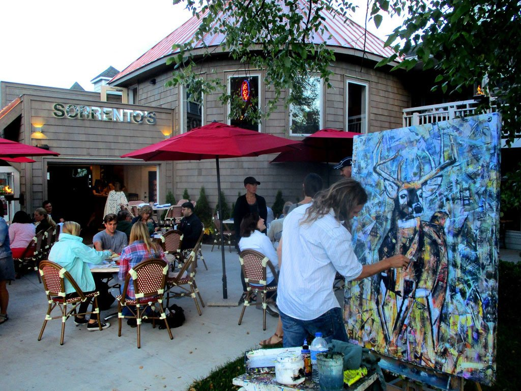 Live painting at Sorrento's Italian Bistro's outdoor patio in downtown Banner Elk, NC by artist K. Paulette. On his easel is 'Collisions of the Heart' painting of a deer buck with antlers. Diners at this fine dining restaurant are eating and watching Kent Paulette paint. A tree hangs over the easel. There are red umbrellas over the tables. Artist is wearing jeans and a white shirt. He has long hair.