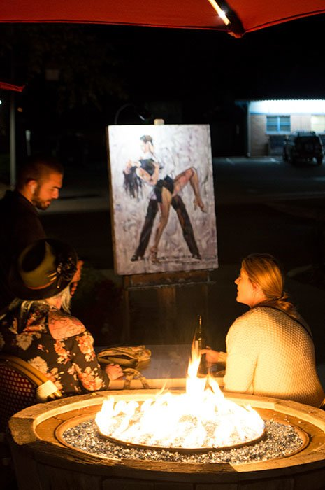 Barra fire pit and Sorrento's outdoor patio at night with artist painting live in downtown Banner Elk, NC.  Three young adults sit around the fire.  On the artist's easel is a painting of tango dancers.