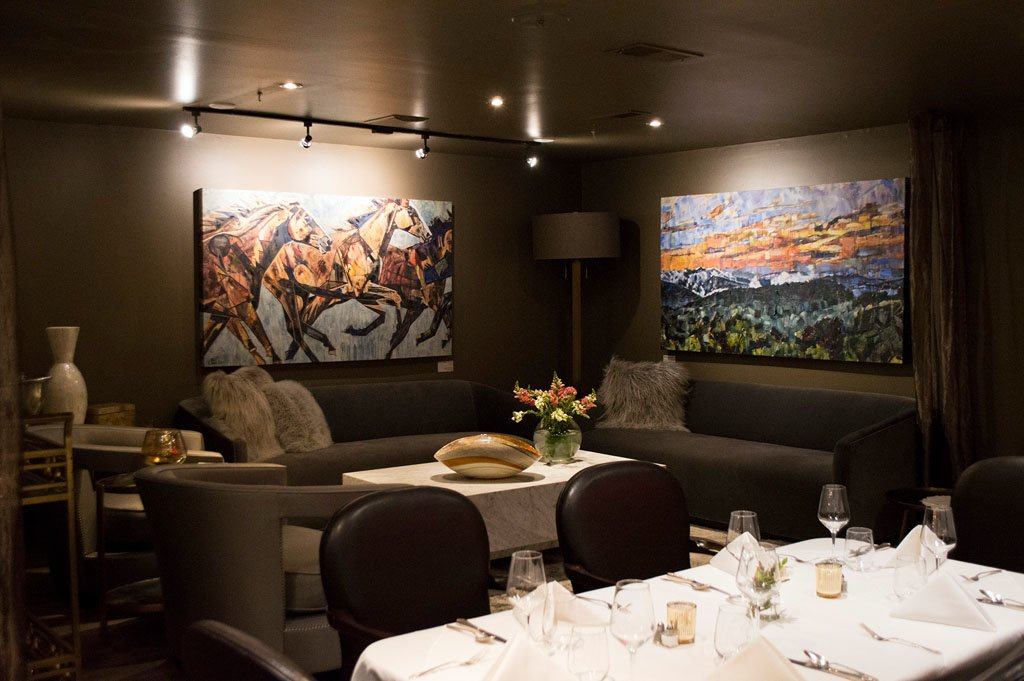 Chef's Table at Sorrento's in Banner Elk, NC features At the Speed of Love painting of horses running and Appalachia Rising mountain landscape painting. Fine Dining Restaurant with grey walls and couches. Flowers in vase and tables set.