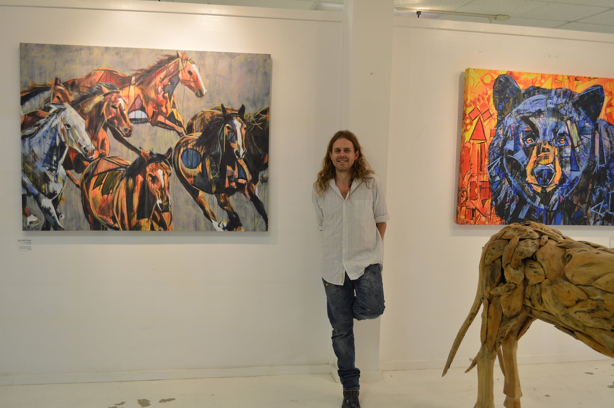 Kent Paulette Art Gallery in Banner Elk, NC. The artist K. Paulette is smiling and standing in front of his painting 'The Wild Tribe' of a stampede of horses. On his other side is his black bear painting 'Quantum Entanglement'. The walls are white. The artist wears jeans and a white shirt. He has long hair.