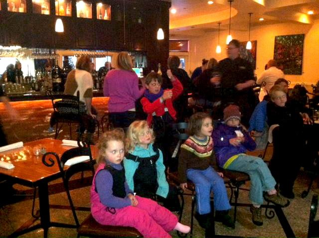 Kids watching artist Kent Paulette paint live at Sorrento's Italian Restaurant.