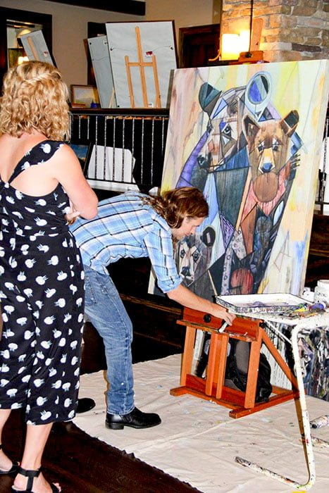 Linville Ridge artist painting live.  Kent Paulette is working on a painting of bears at the country club which also has golf.  It is located in Banner Elk, NC in the mountains.  A young woman is watching the artist paint.