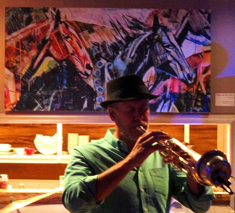 Shane Chalke playing trumpet during BE Jazz Night at Chef's Table in Banner Elk. Painting of horses running behind the trumpeter.