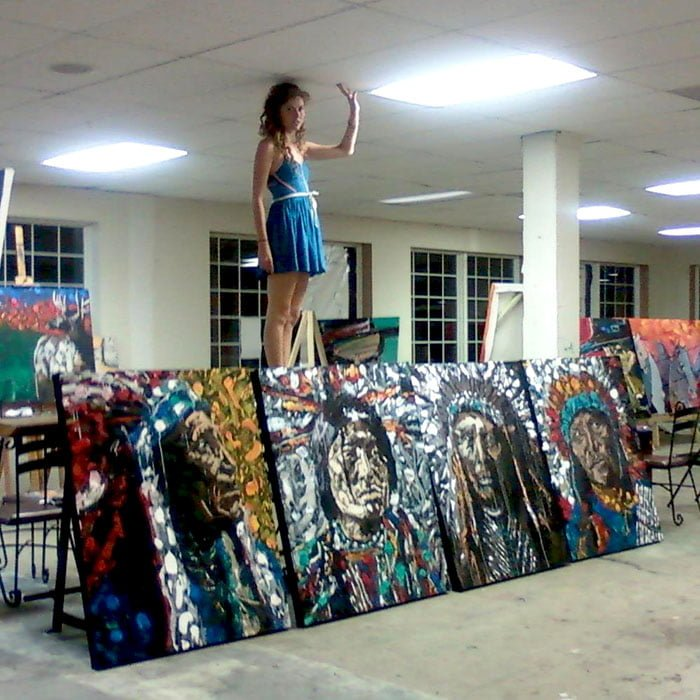 A young woman standing on a table over four large paintings of Native Americans.