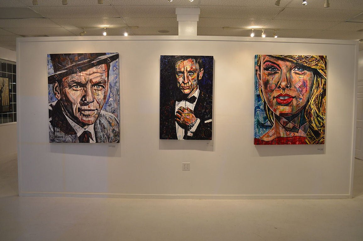 Kent Paulette Art Gallery in Banner Elk, NC features paintings of Frank Sinatra, James Bond, and Taylor Swift. Three colorful paintings hanging on a white wall.